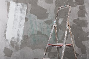 Old painted and stucco ladder on concrete wall background