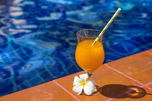 Glass of fresh cool orange juice drink flower swimming pool