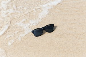 Black sunglasses on beach in water