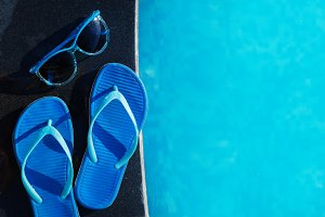 Blue slippers and sun glasses near swimming pool holiday concept
