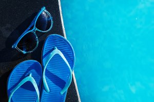 Blue slippers and sunglasses on pool