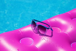 Sunglasses and pink mattress on pool