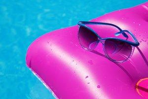 Sunglasses and pink mattress on pool