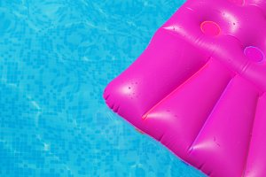 Pink air mattress in swimming pool. Holiday background.