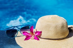 Sunglasses with flower and straw hat on a swimming pool