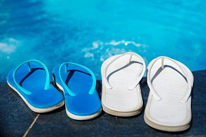 Beach slippers on border of swimming pool