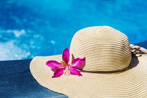 Straw hat with orchid flower near swimming pool holiday concept