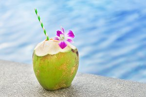 Fresh coconut drink with orchid flower swimming pool