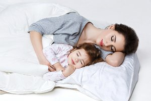 Beautiful mother and daughter in bed