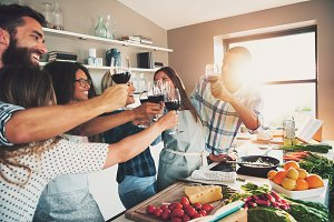 People toasting wine glasses at kitchen counter