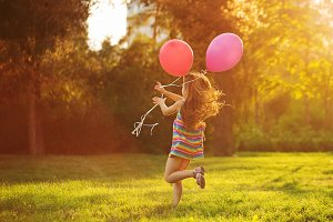 Little girl runs with balloons