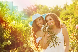 Two sisters with flowers.