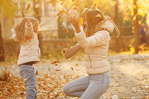Mother and daughter throw up leaves