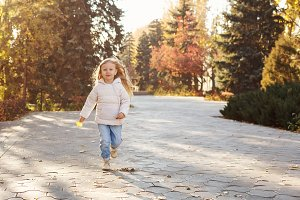 Little girl running in autumn park.