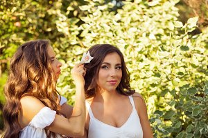 Girl weaves flowers in hair sister