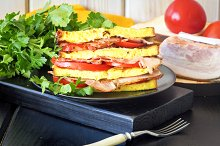 Tasty sandwich with french toast, fried bacon and tomatoes for breakfast or lunch