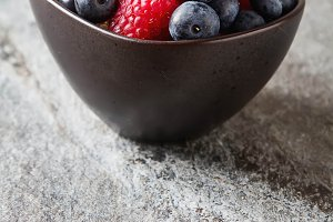 Ripe berries. White, red raspberries and blueberries in brown bowl. Grey stone background.