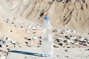 Bottle of water in desert land - hydration and dehydration concept