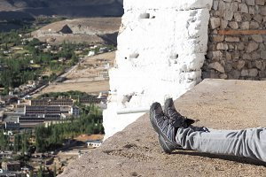 Hiker's boots relaxing and resting his feet on high mountain trekking scene and adventure