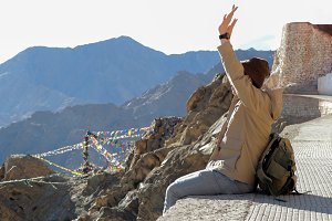 Male traveler raising hands as he successfully climbed up to the top of high mountain