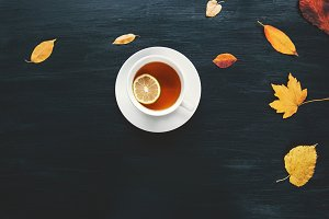 Cup of Tea with leaves on dark table