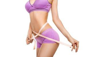 model measuring her waist