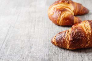 French food for breakfast. Fresh baked croissants. Light wood background.