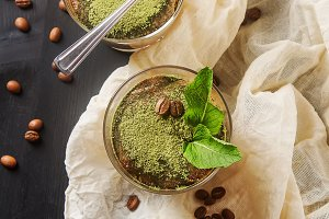 Traditional Italian cuisine. Dessert chocolate tiramisu, mint tea matcha. Coffee beans. Black wood background.Fabric milky. Top view.