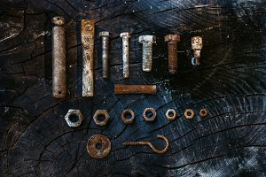 Set of rusty screws on a dark wooden