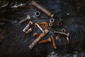 Set of rusty screws on a dark wooden