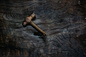 Rusty hammer on a dark wooden