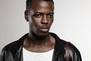 Human face expressions, emotions and feelings. Young handsome fashionable African man dressed in t-shirt and leather jacket, standing against white wall background, looking serious and thoughtful