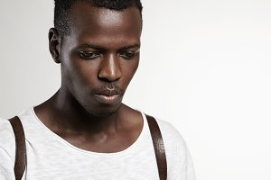Portrait of good-looking attractive dark-skinned male model wearing white t-shirt, looking down with serious expression, posing against studio wall background with copy space for your advertisement