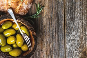 Green olives and slices of ciabatta