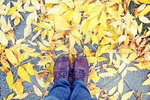 Shoes on yeallow leaves at autumn
