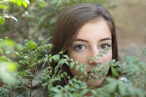 Face of a young woman between leaves