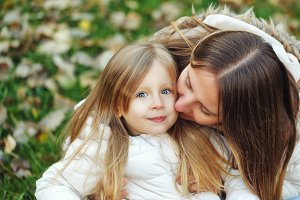 Mother hugging and kissing daughter