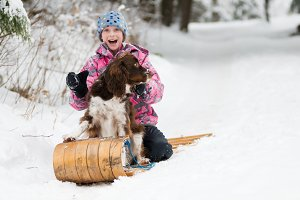 girl sledding with her dog in winter