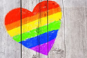 Rainbow heart drawing on grungy wood