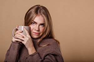 Girl in warm sweater drinking tea