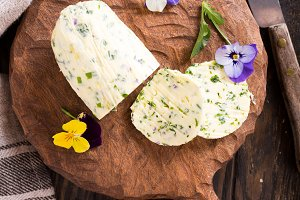 Herb butter with edible flowers on wooden cutting board