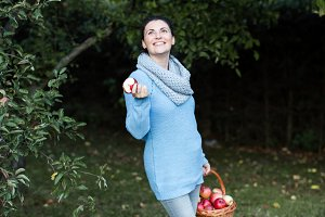 Woman holding basket biting apple