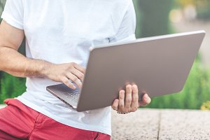 Young man holding modern Laptop