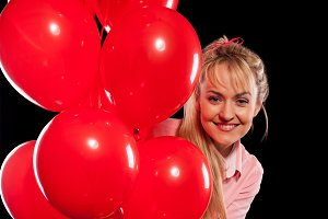 woman looking out of red balloons
