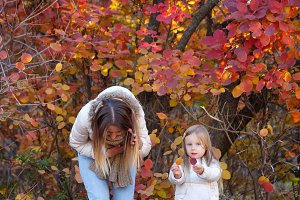 Mother and daughter collect leaves