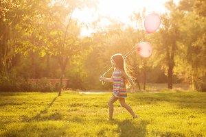 Little girl running with a balloon