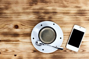 Cup of coffee and phone on a table