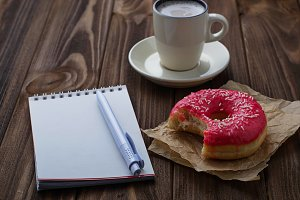 Donut, cup of coffee and notebook