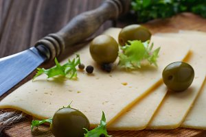 Sliced cheese and green olives