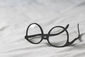 Eyeglasses on messed bed.